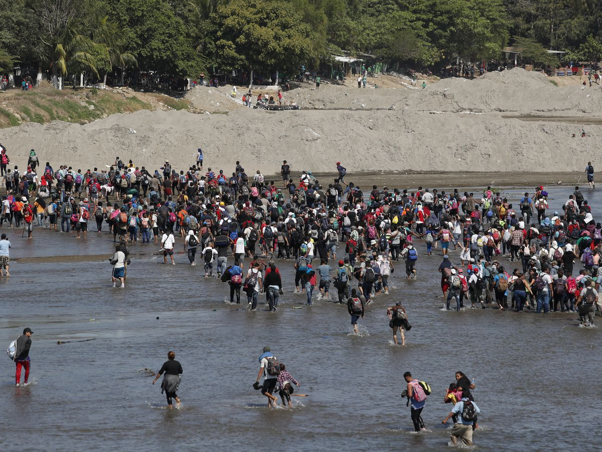 Migrants ford river from Guatemala to Mexico