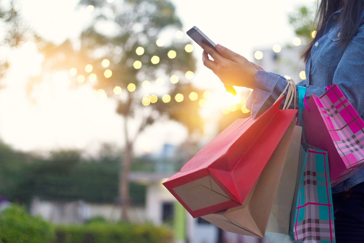 Woman using smartphone with shopping bag in hands
